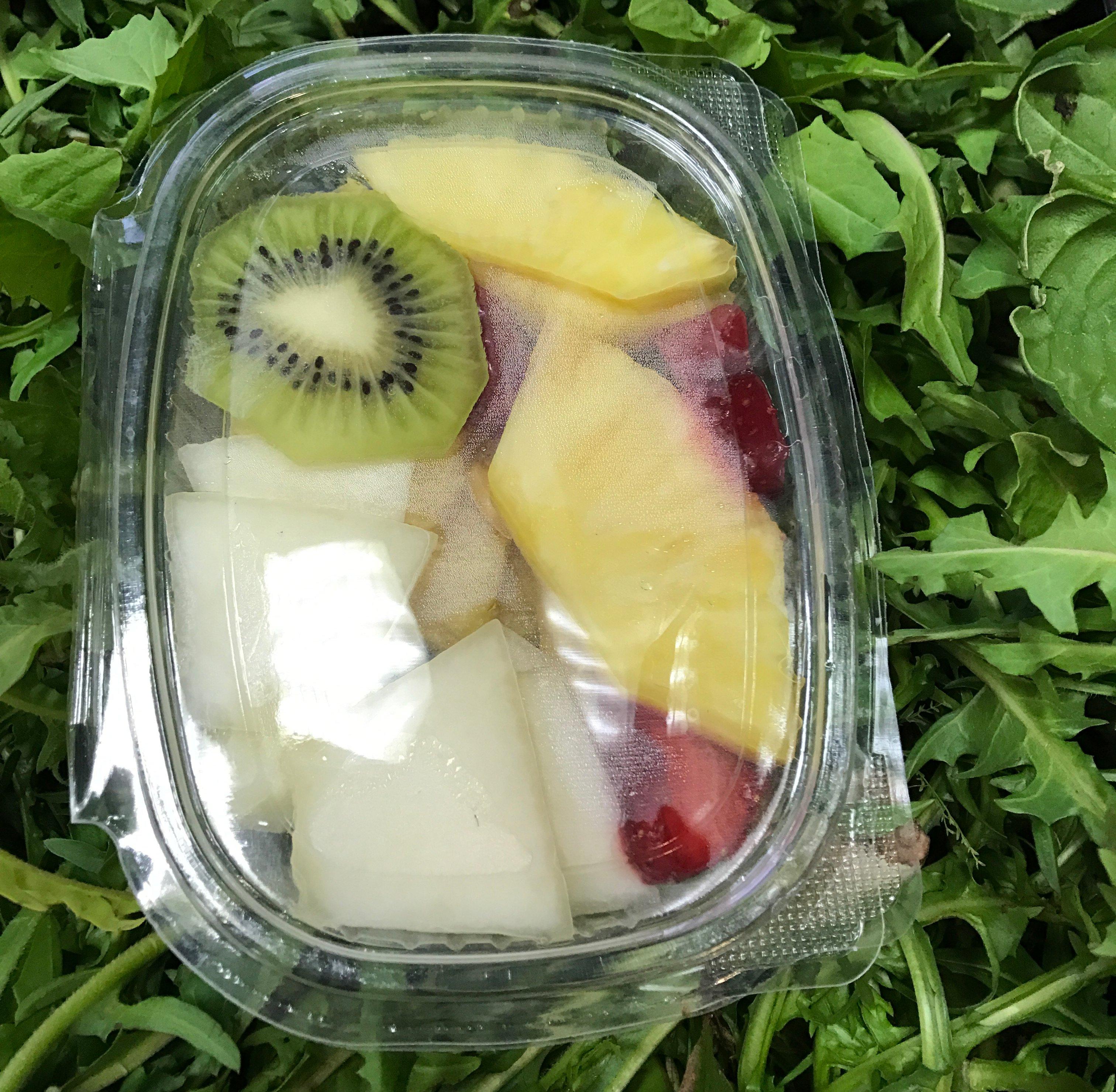 Primo piano di una cassa di plastica con assortimento di frutta tagliata