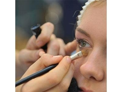 mani che sfumano l`ombretto sotto un occhio di una donna con un pennellino professionale
