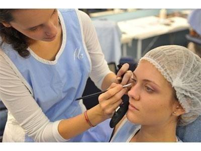 truccatrice mentre sistema il trucco  con un pennello professionale per il make up