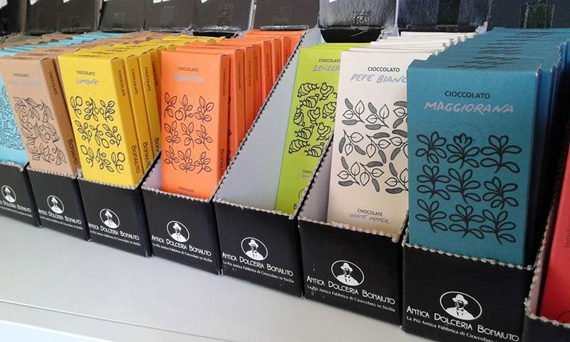 contenitori di cartone di color nero con confezioni di cioccolato incartate  di vari colori e giusti come Limone, arancia, zenzero, pepe bianco e maggiorana