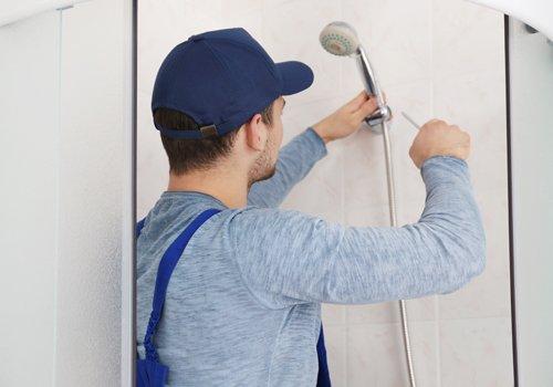 un uomo mentre ripara una doccia