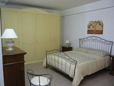 Camera da letto con letto in ferro battuto e armadio giallo