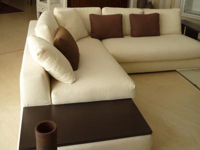 un divano angolare di color bianco con i cuscini di color marrone