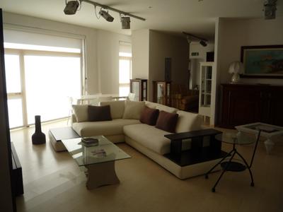 una sala con un divano di color bianco e altri mobili in legno