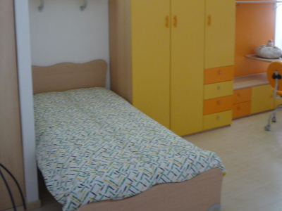 Cameretta con letto singolo e armadio giallo