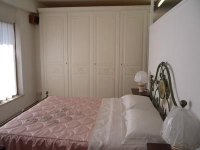 Una camera con un letto in ferro battuto e un armadio di color bianco