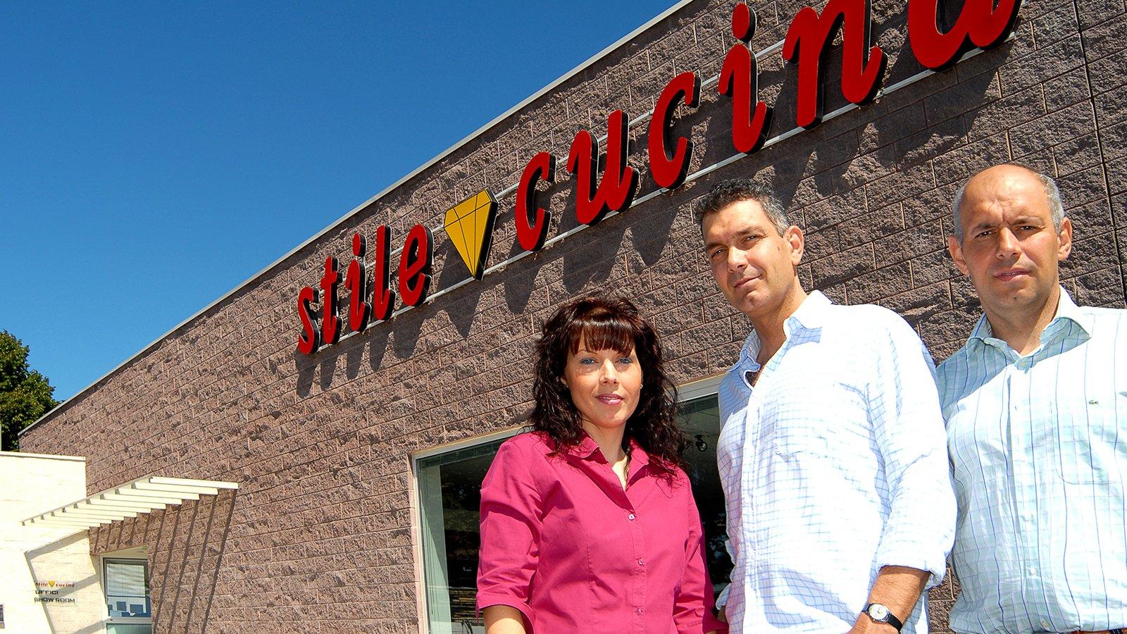 Una donna e due uomini davanti a uno showroom e una scritta Stile Cucina