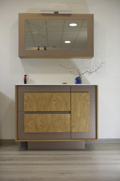 Un lavandino con un mobile in legno e un mobile con specchio al muro