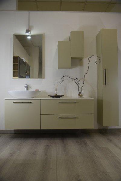 Dei mobili da bagno di color beige, un lavandino ovale e uno specchio al muro