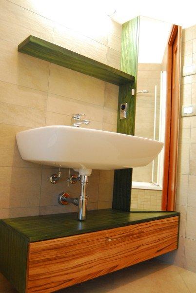 Un mobile da bagno di color marrone e verde scuro e un lavandino bianco con dei tubi a vista