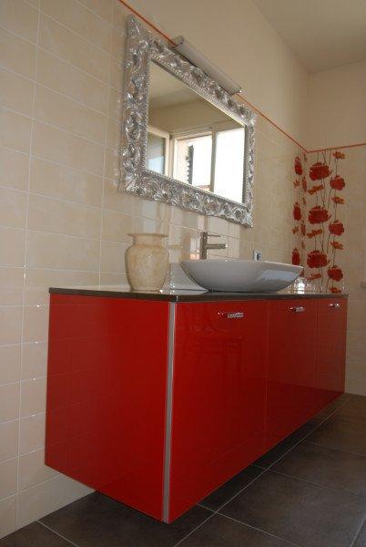 Un mobile da bagno di color rosso con un lavabo ovale e uno specchio con cornice argentata