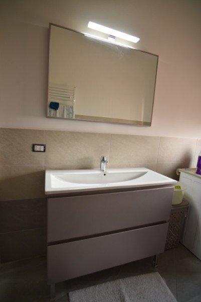 Un lavandino con sotto un mobile di color grigio e uno specchio a forma quadra al muro