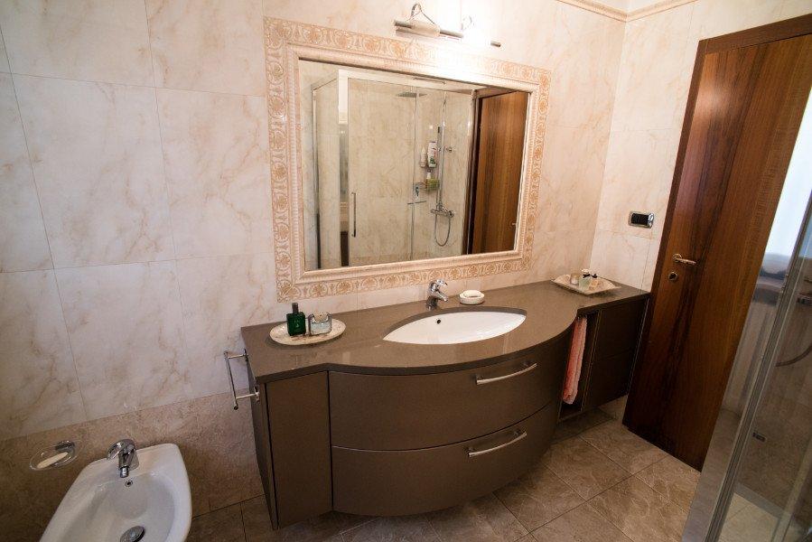 Un bagno con mobili di color beige con dei cassetti, un lavandino sopra e uno specchio al muro