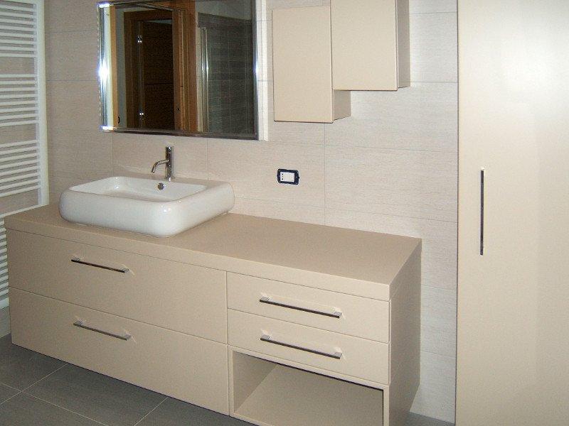 Un bagno con lavandino ,un mobile sotto di color grigio scuroe un mobile in legno sulla destra accanto uno box doccia