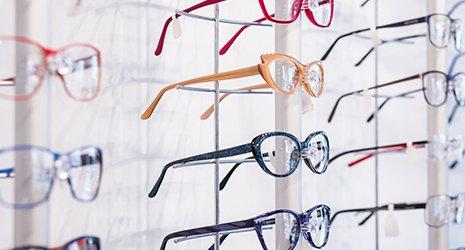 degli occhiali da vista di diversi colori in esposizione su un pannello