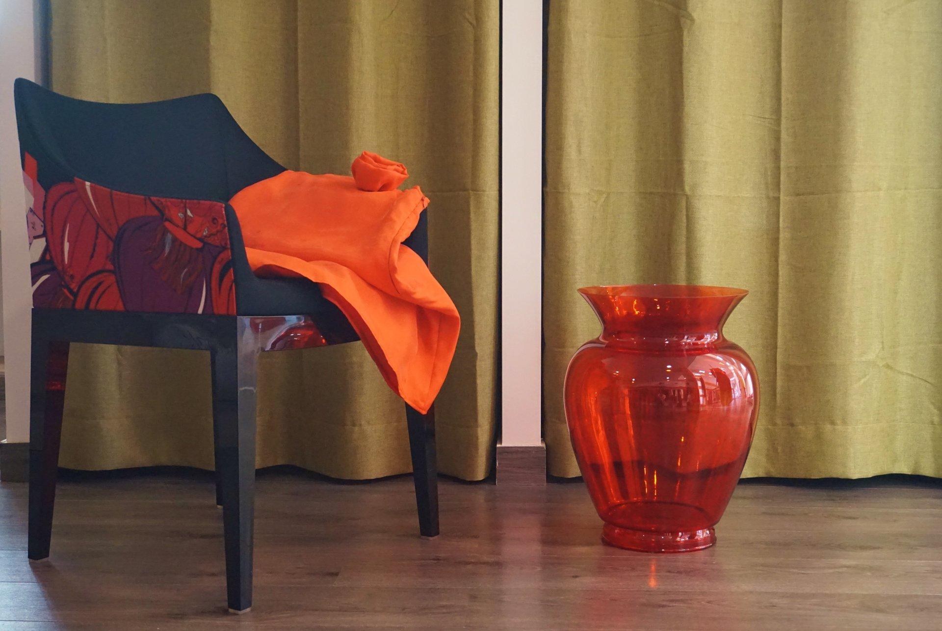 sedie nera con sopra panno arancione e vaso arancione