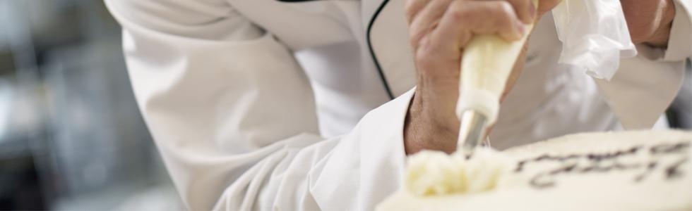 cuoco mette della crema pasticcera su una torta