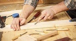 un falegname lavora ai dettagli di un'anta in legno