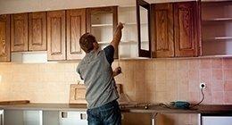 un uomo monta un'anta di un mobile in cucina