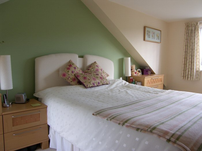 Bedroom with green wall and bed