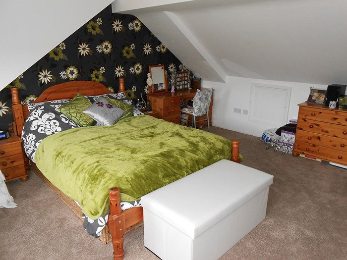 Green bed and floral wallpaper in conversion