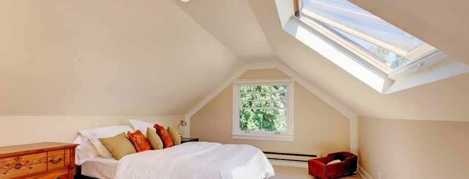 Masard loft conversion with bed and large windows