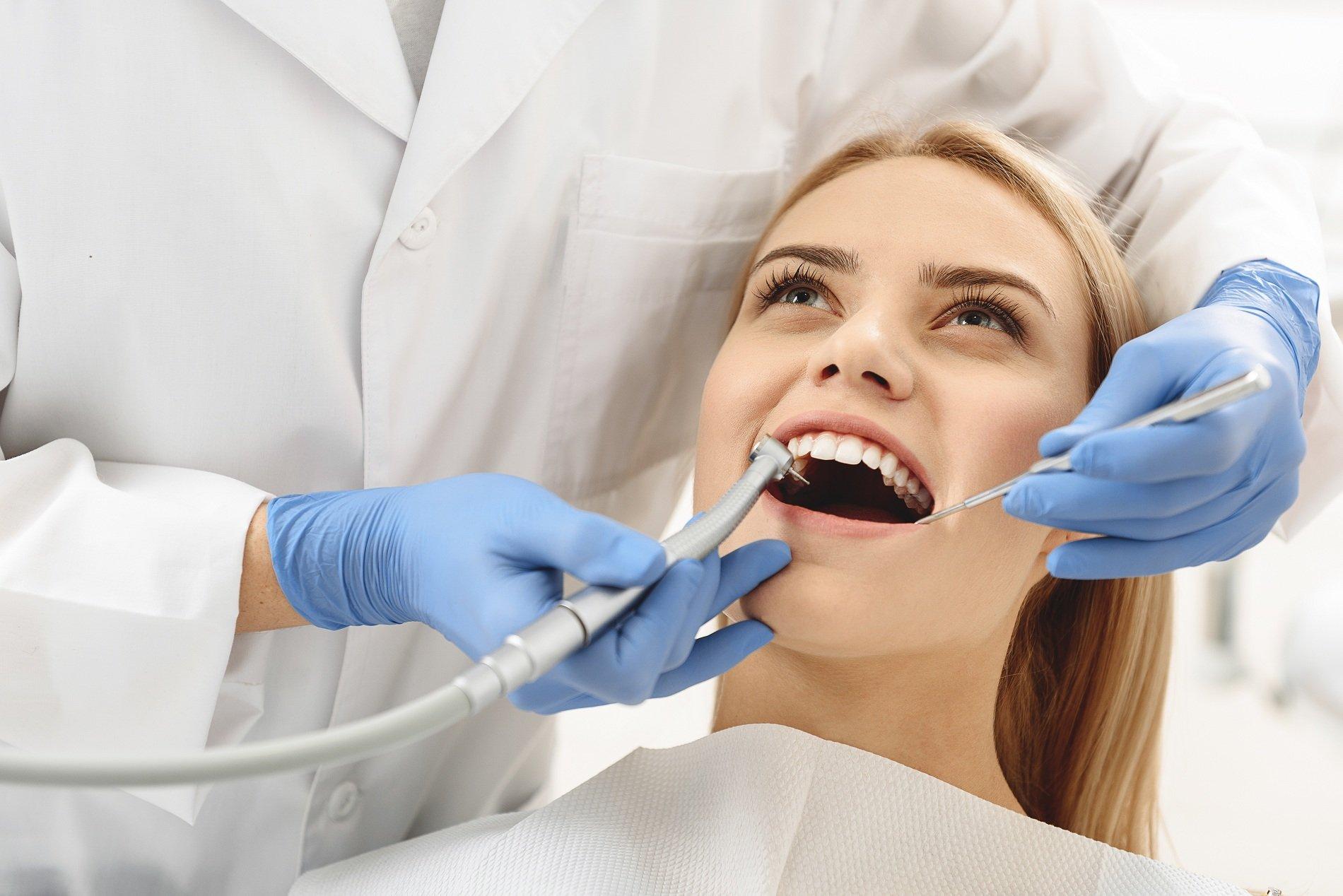 dentista opera sui denti di una paziente
