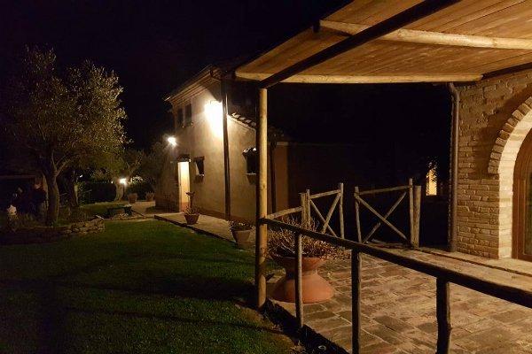 visto di un giardino con un ulivo e due edifici illuminati durante la sera