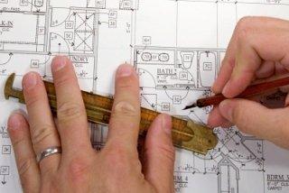 mani mentre disegnano un progetto su carta
