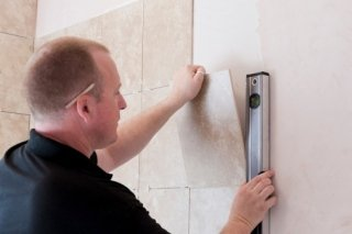 addetto mentre misura una mattonella da attaccare al muro