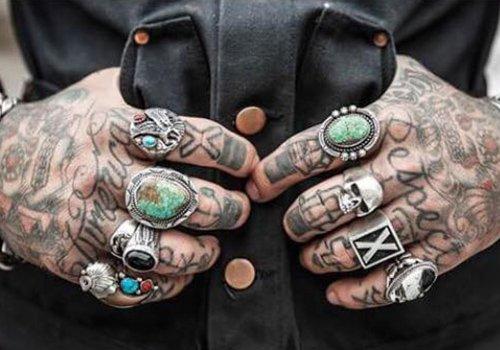 due mani tatuate con degli anelli