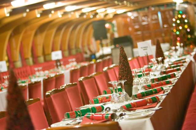 Tables decorated with Christmas trees and crackers