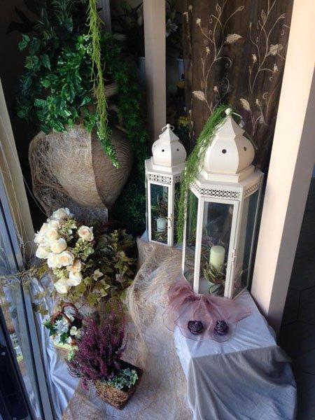 tavolo allestito con fiori e due lanterne con all'interno due candele