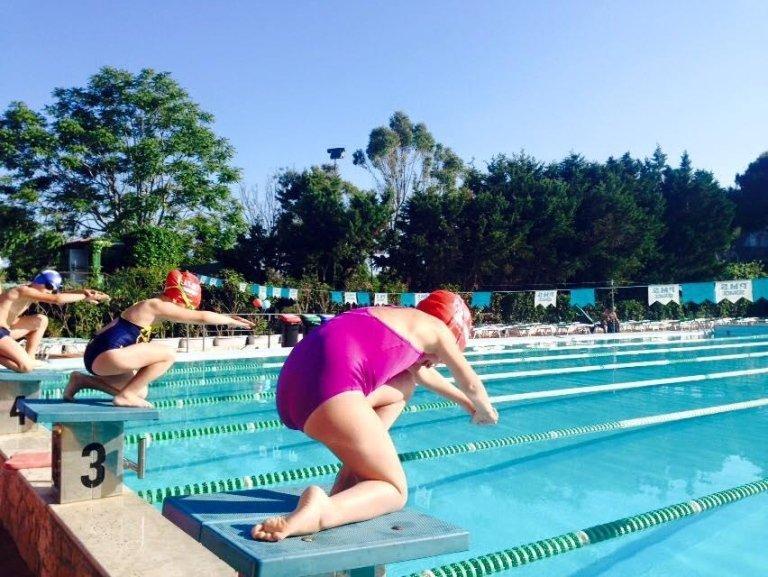 gente mentre saltano in piscina