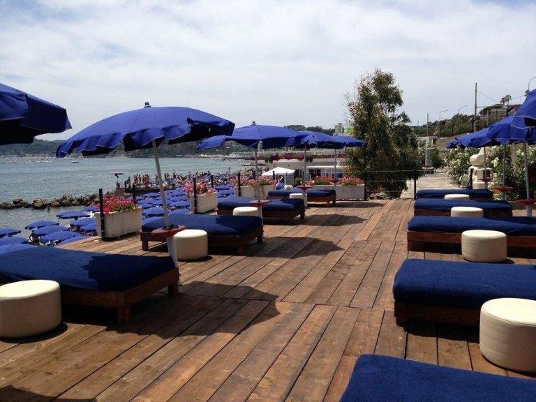 fila di lettini e ombrellini da spiaggia sul pavimento di legno con fiori