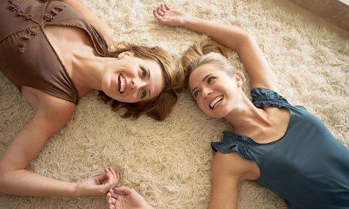 Two girls lying on rug
