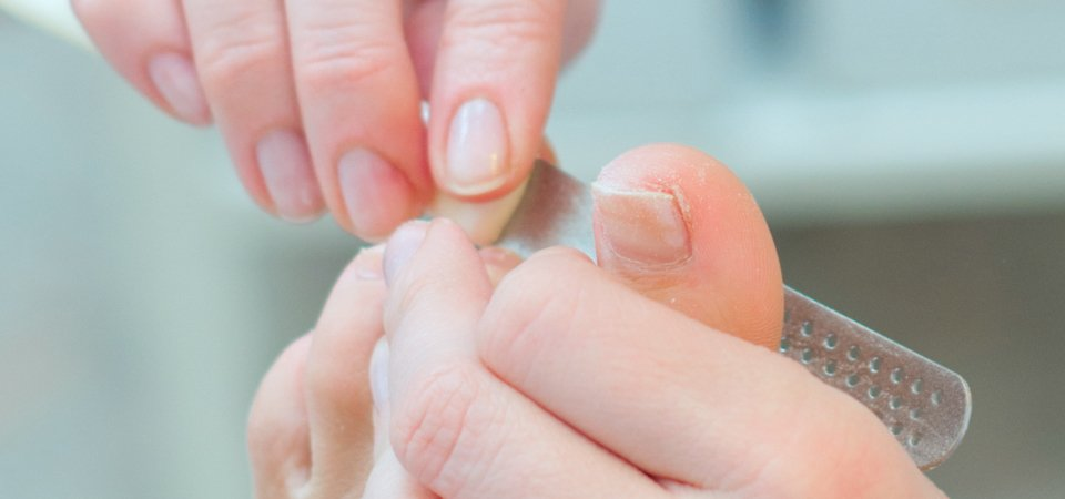 Close up of toenails being filed