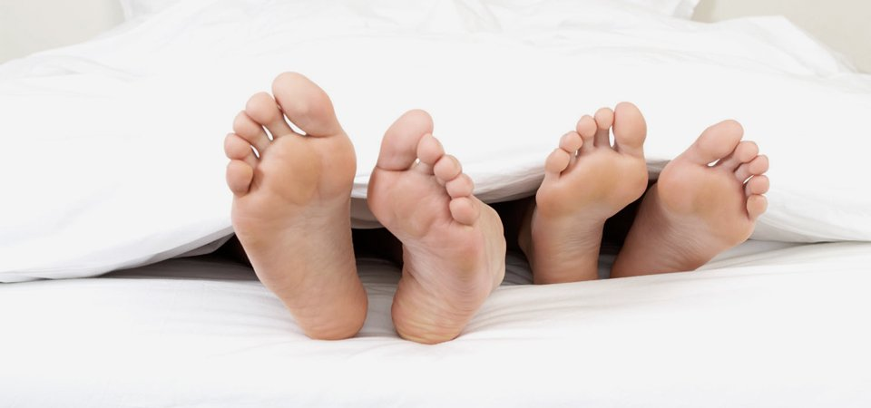 Two pairs of feet sticking out of a bed sheet