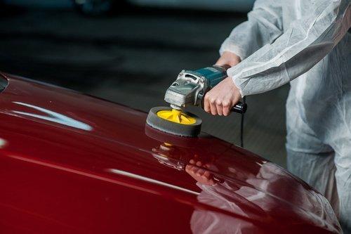 Tecnico durante la riparazione di un'ammaccatura sul cofano di un auto rossa