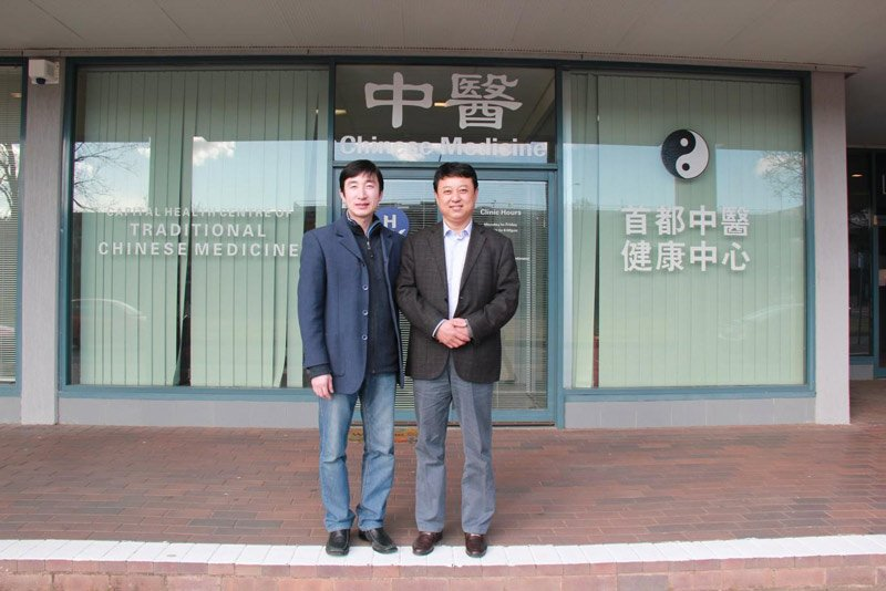 two men outside a traditional chinese medicine office