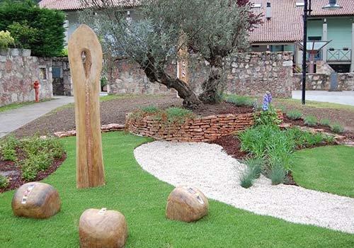 un giardinetto con delle rocce, delle piantine e un ulivo