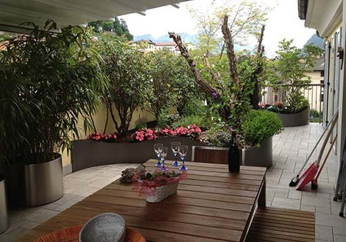 un tavolo in legno all'esterno con dei bicchieri, una bottiglia e delle piante