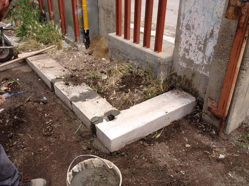 un'aiuola a muretto con terra e erba