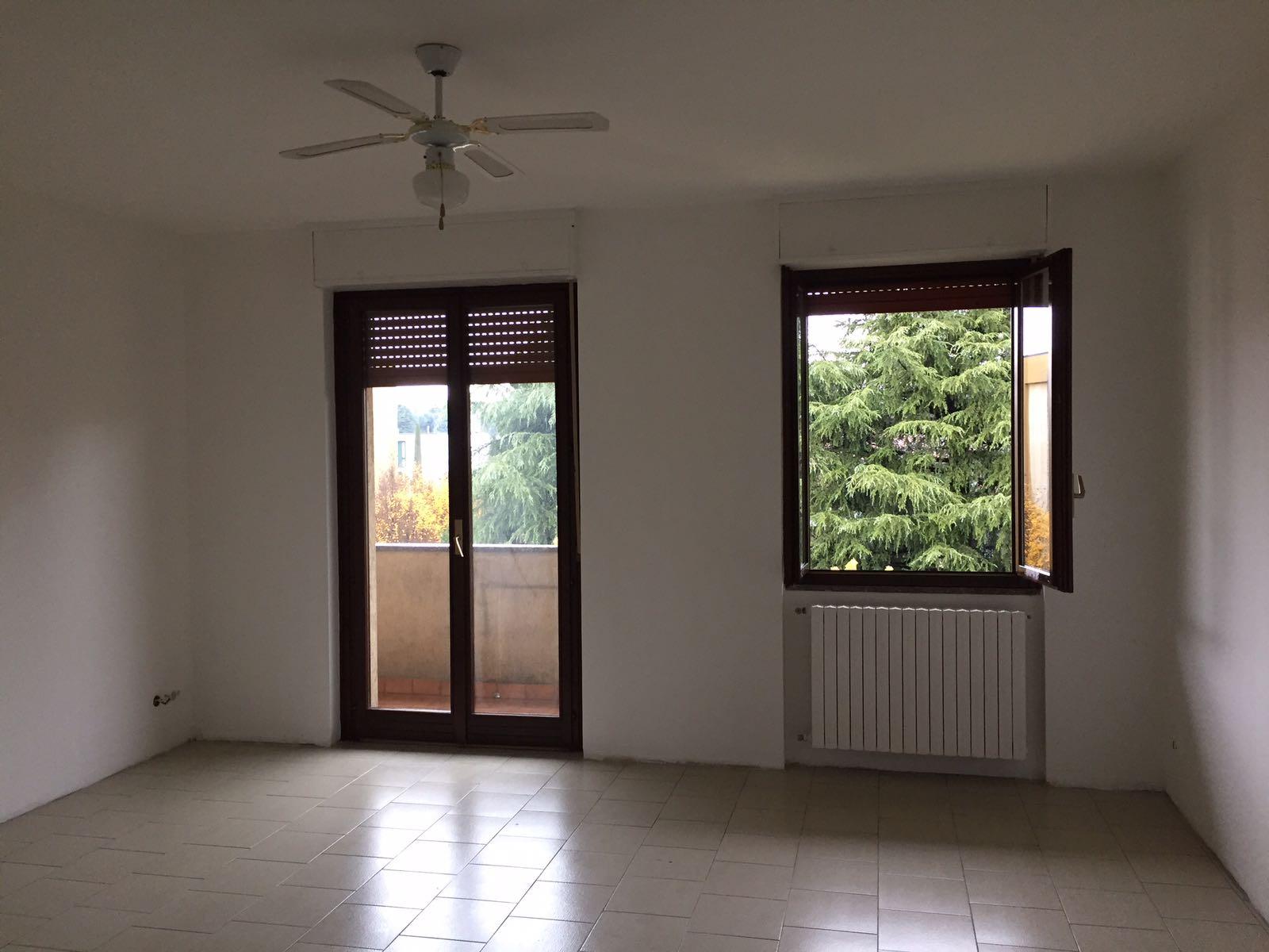 vista di una casa con due finestre, un calorifero e un ventilatore sul soffitto