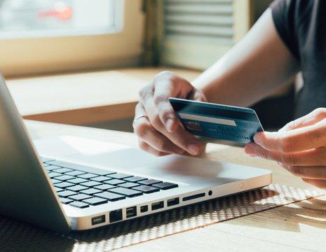 Mani femminili tengono una carta bancaria di fronte a un laptop