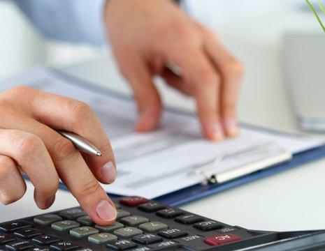 Mani maschili lavorano su una calcolatrice