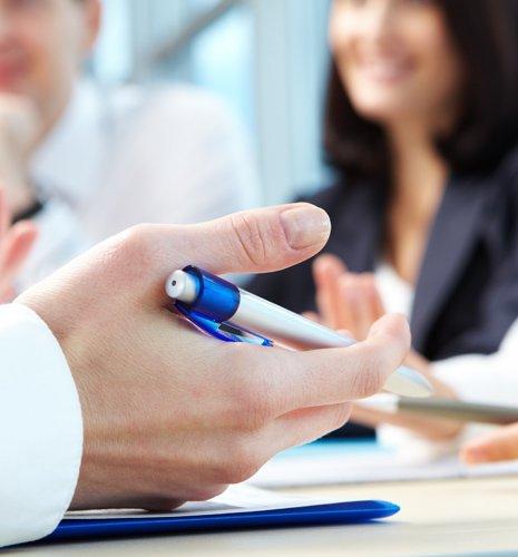Mano maschile tenendo una penna durante una riunione