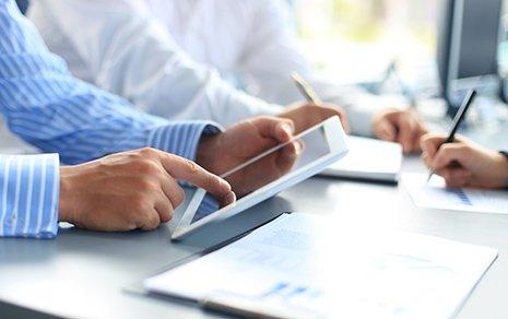 Uomo d'affari lavora sul tablet durante una riunione