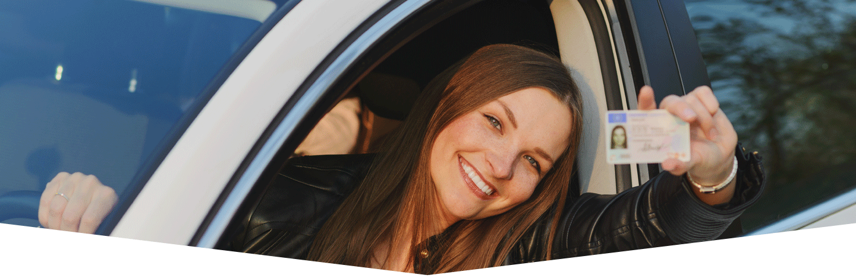 donna al volante mostra la sua patente di guida