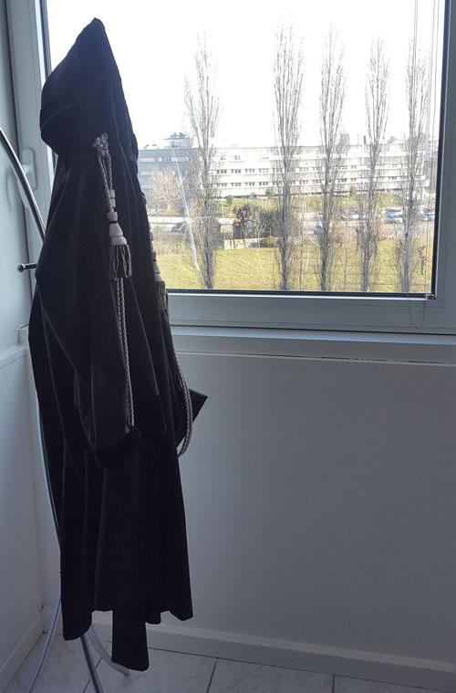 una tunica nera  appesa e vista di una finestra da cui si vede l'esterno con degli alberi e in lontananza uno stabile con facciata bianca